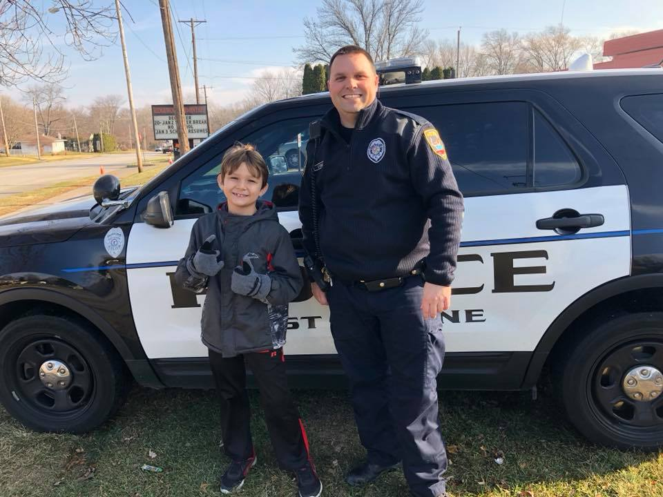 Police Officer Standing with a Young Boy